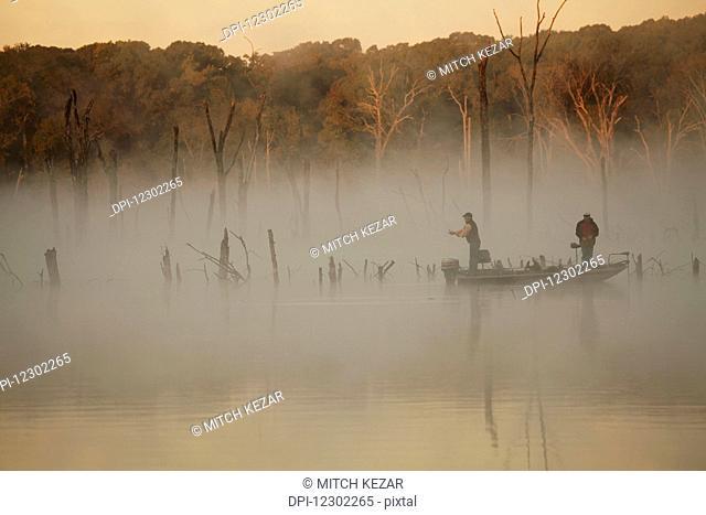 Bass Fishermen Fishing On Lake On A Foggy Morning