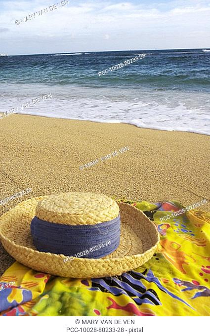 Straw hat with blue band on colorful pareo sarong with hand painted kukui nut lei, beach, ocean and sky background