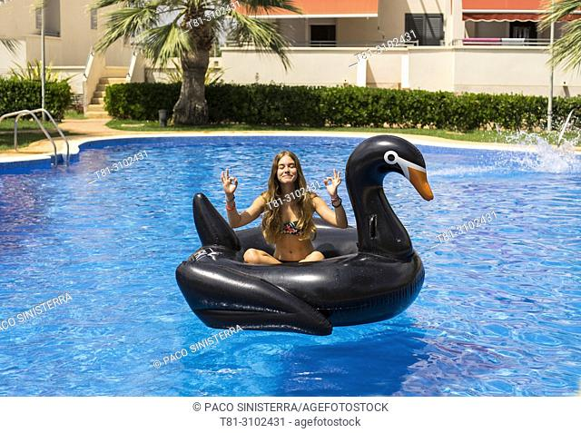girl doing yoga in the pool, with an inflatable duck, Valencia, Spain