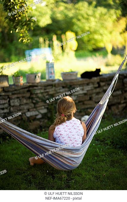 Teenage girl sitting in a hammock Sweden