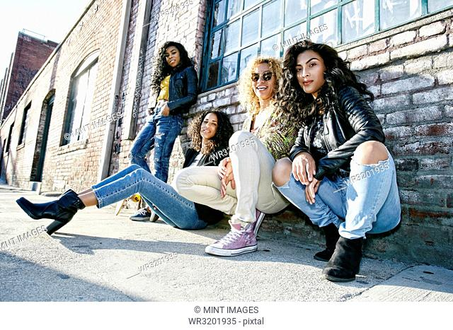 Four young women with curly hair sitting side by side on steps outside a building