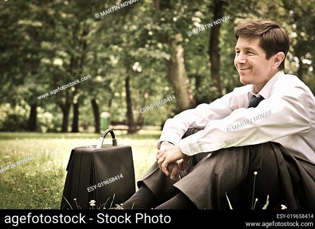 Senior business man siting in grass
