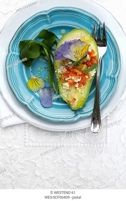 Stuffed avocado with goat's cheese and edible blossoms on plate, elevated view