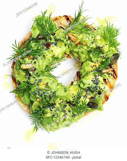 A grilled bagel with avocado cream and dill (close up)