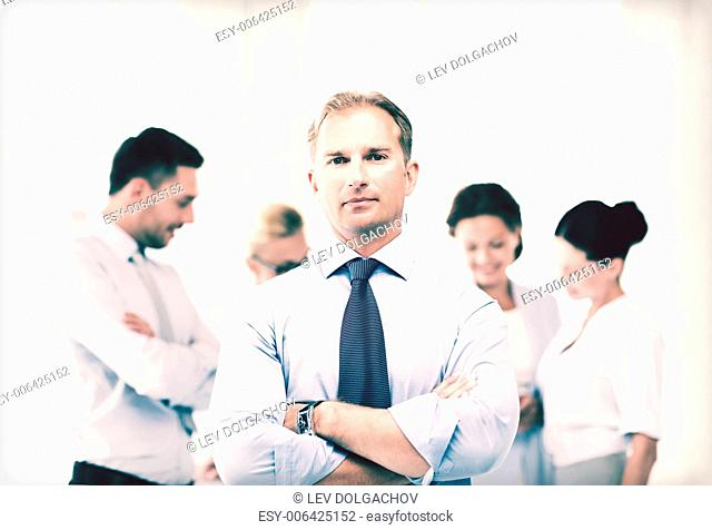picture of handsome businessman with team in office