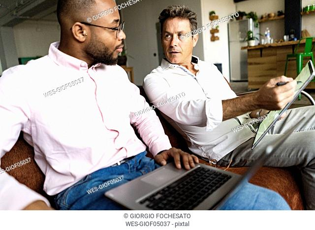 Two businessmen using laptop and tablet on sofa in loft office