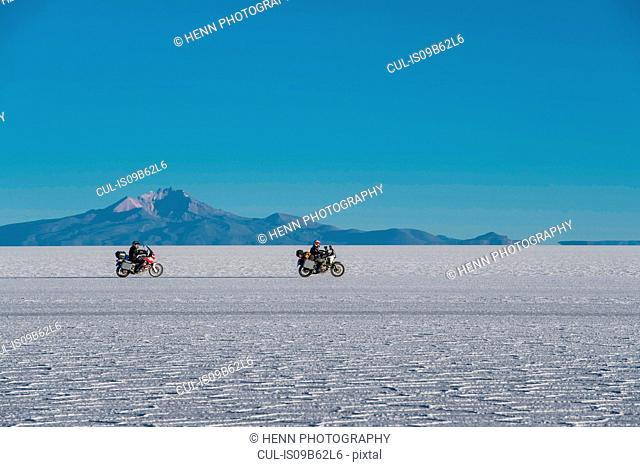 Two men riding motorcycles on the salt flats of Uyuni, Potosi, Bolivia, South America
