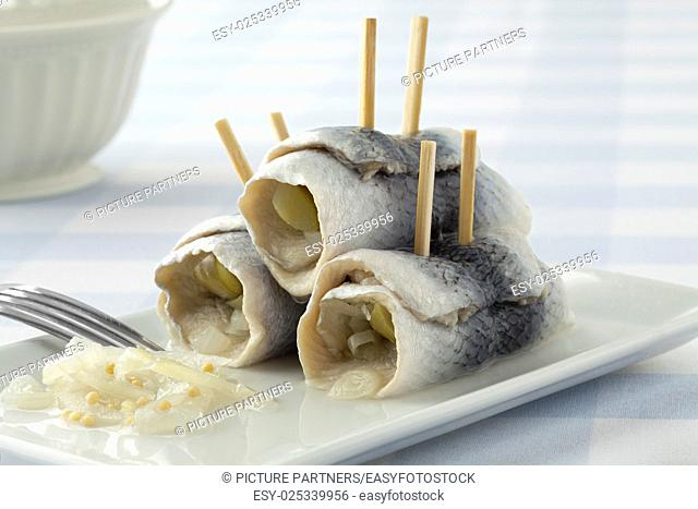 Traditional rollmops,stuffed pickled herring fillets,on a dish