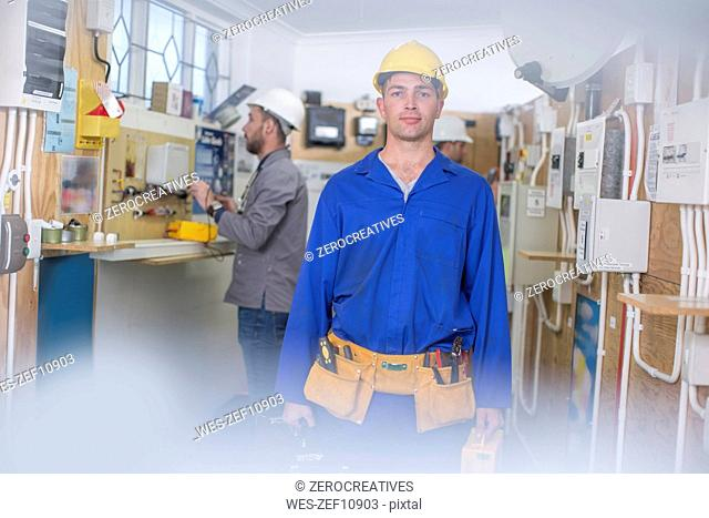 Electrician training, student with hardhat and toolbelt