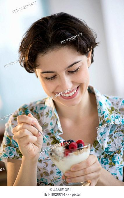 Woman eating yogurt with fruits