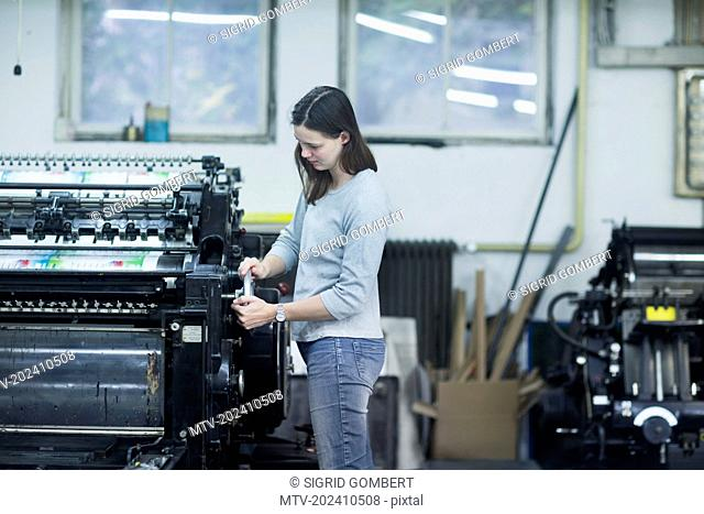 Print worker adjusting printing machine in an industry, Freiburg im Breisgau, Baden-Württemberg, Germany