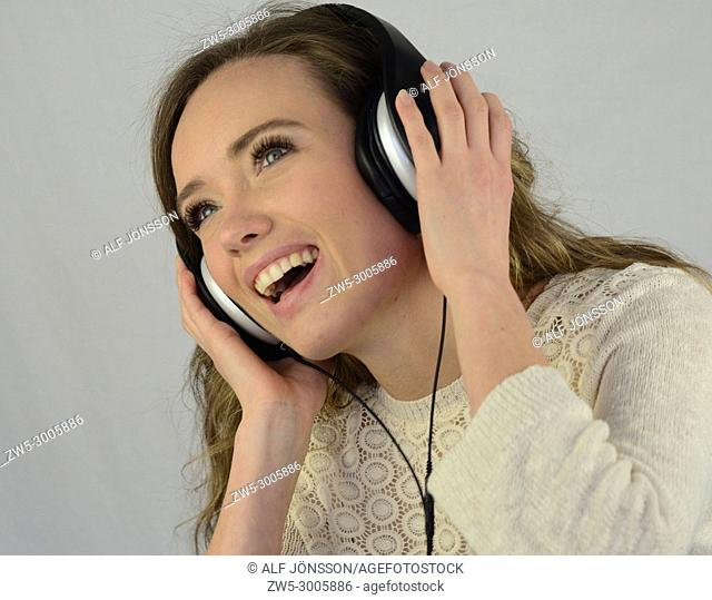 Young happy woman listening to music in headphones