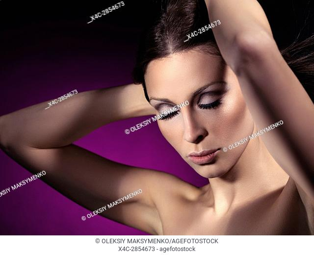 Beauty portrait of a young woman with closed eyes and artistic makeup and long eyelashes on purple background