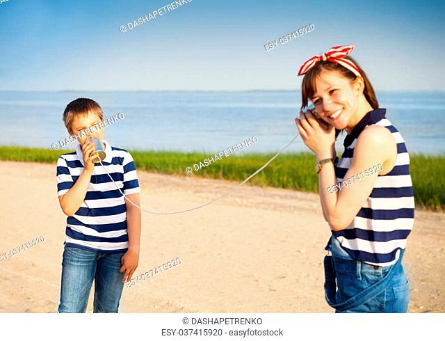 97f5f2a447 Kids having a phone call with tin cans on sea background