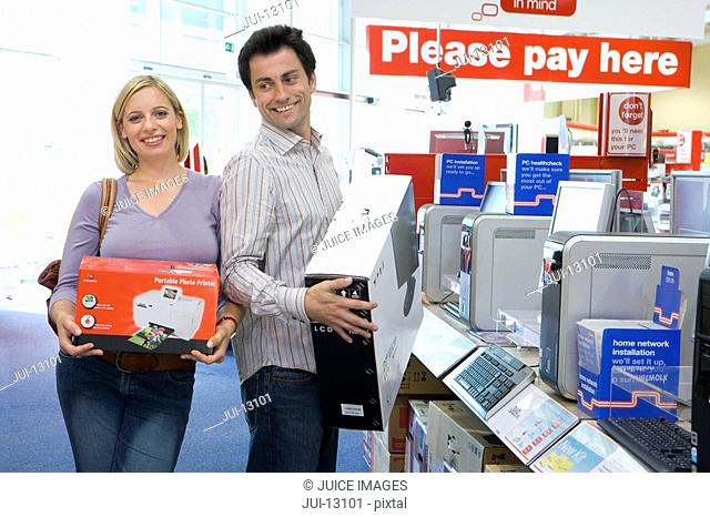 Young couple shopping, woman with printer in box, man with computer in box, smiling, portrait