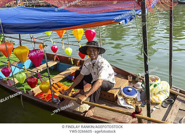 Vietnameses fisherman sitting in his fishing boat decorated with coloured lanterns, on the Son Thu Bon River, Hoi An, Quang Nam Provence, Vietnam, Asia