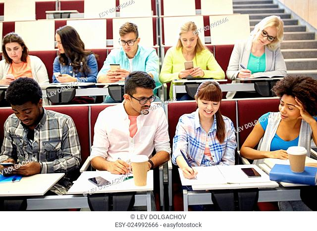 education, high school, university and people concept - group of international students with notebooks, smartphones and coffee at lecture hall