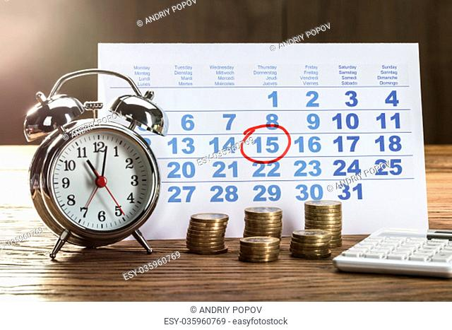 Tax Time On Alarm Clock With Coins, Calculator And Calendar Over The Wooden Table