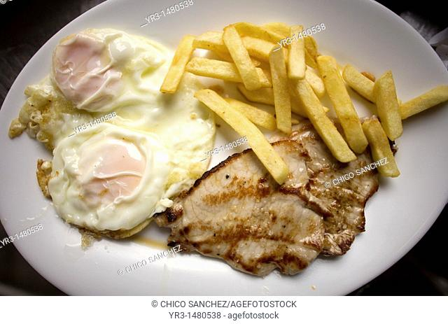 A combination plate or plato combinado with fried eggs, fried potatoes and tenderloin sit in a restaurant of Cordoba, Andalusia, Spain, april 18, 2011