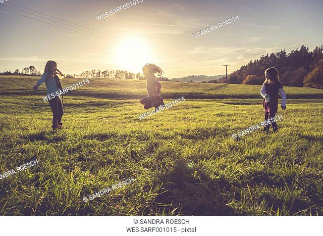 Three little girls playing with a spiral on a meadow in backlight