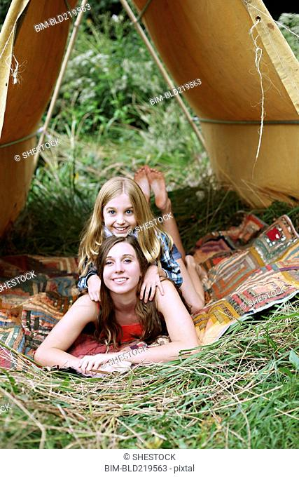 Sisters laying in camping tent