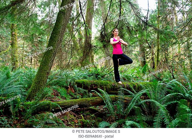 Mature woman performing tree pose in forest