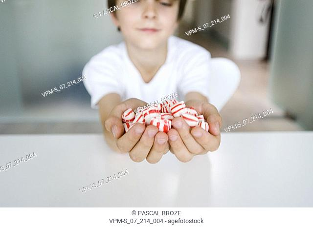 Close-up of a boy holding a handful of candies