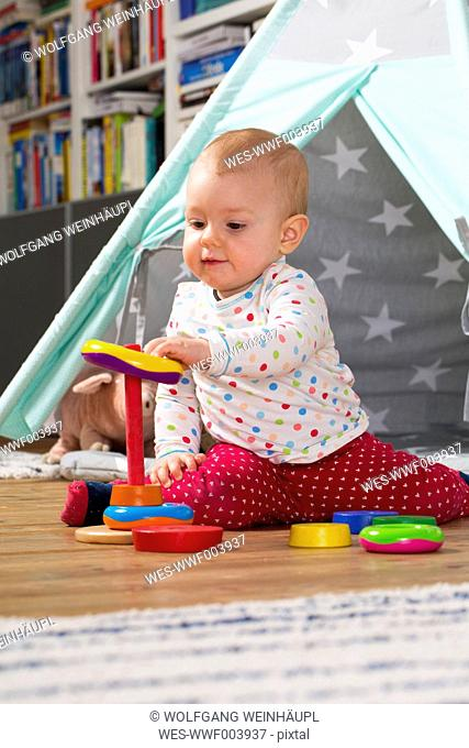 Baby girl playing with wooden toys on the floor at home
