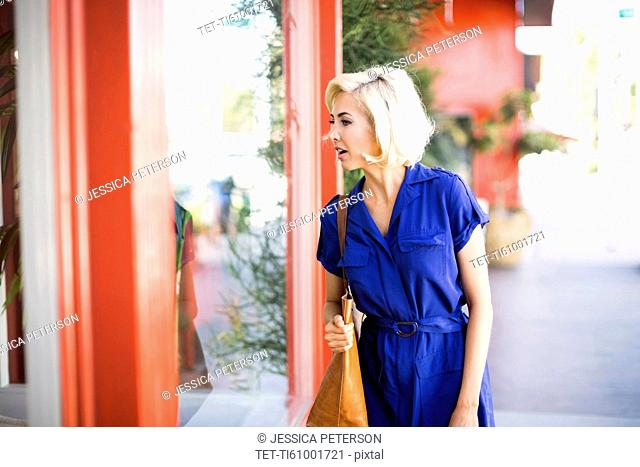 Woman in blue dress looking at window display