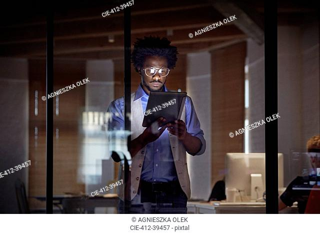 Design professional working late, using digital tablet in dark office at night