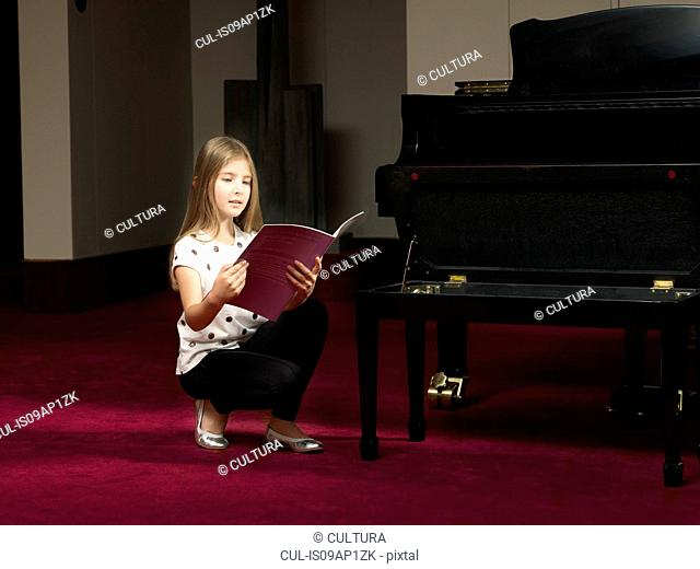 Girl crouching on stage reading sheet music for piano