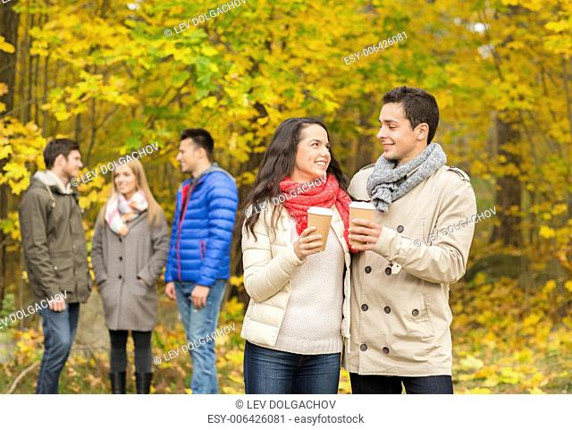 love, relationship, season, friendship and people concept - group of smiling men and women walking with paper coffee cups in autumn park