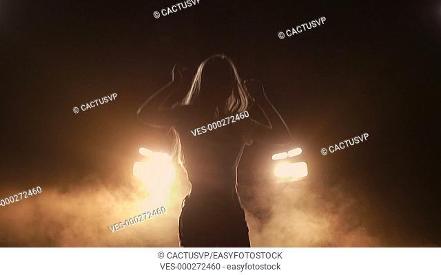 Joyful woman dancing in car headlights at night