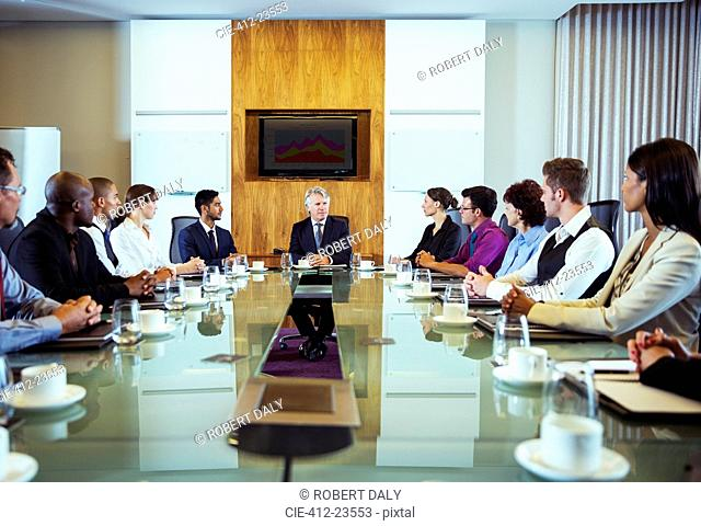 Conference participants looking at man sitting at head of conference table