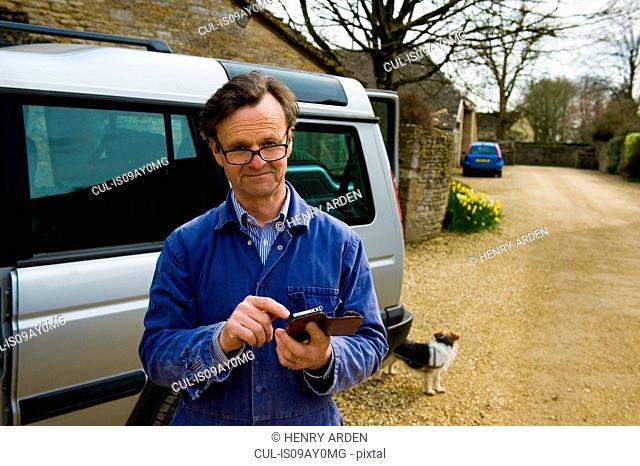 Portrait of farmer outside farmhouse texting on smartphone