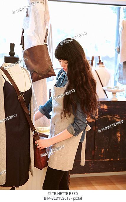 Mixed race employee arranging purse in clothing store