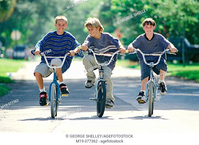 three kids riding their bikes
