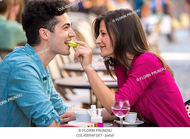Young couple eating macaroon at pavement cafe, Paris, France