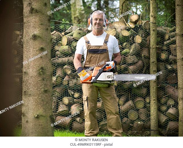 Man holding chain saw by firewood