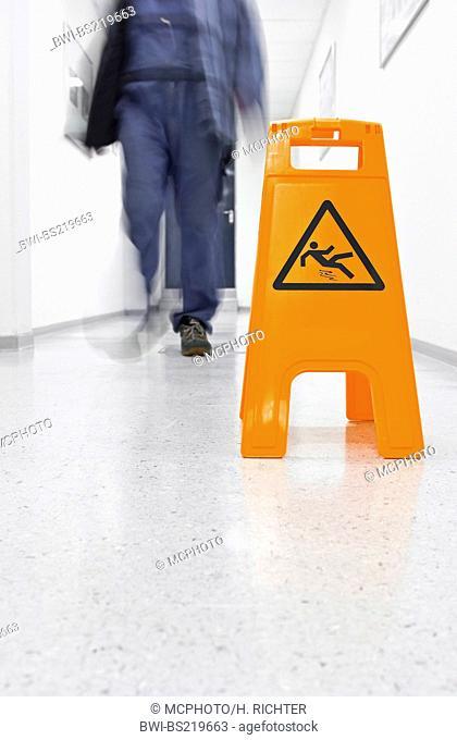 man passing warning sign in a corridor saying 'attention - slip hazard'
