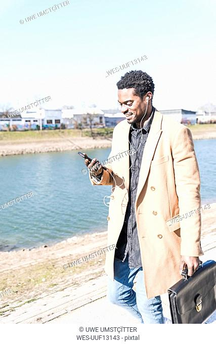 Smiling businessman walking at the waterfront with briefcase, cell phone and earphones