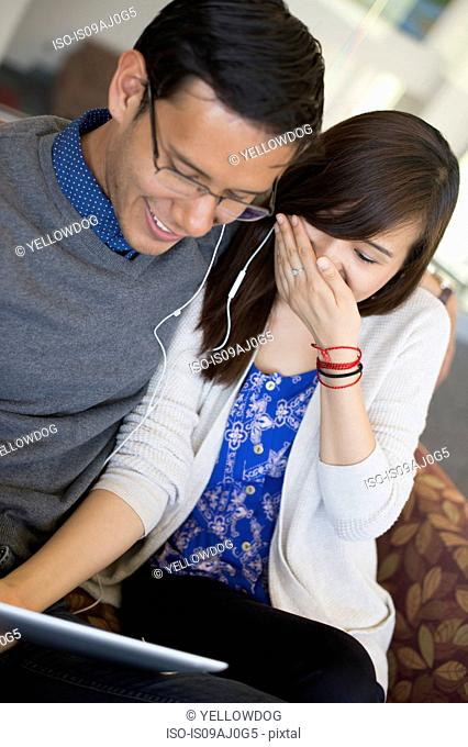 Young couple using digital tablet, laughing