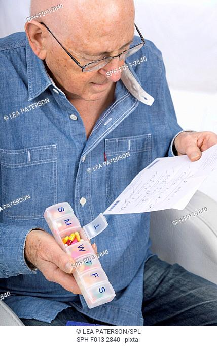 MODEL RELEASED. Senior man holding a prescription and pill organiser