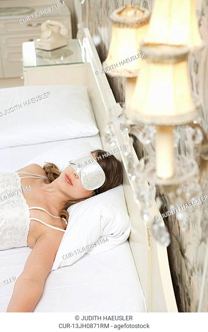 woman on hotel bed with sleeping mask