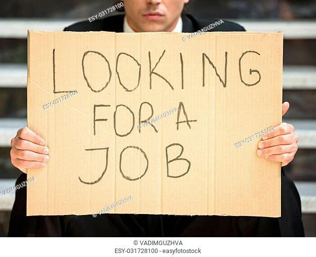 Close-up of man in suit sitting at stairs with sign in hands. Unemployed man looking for job