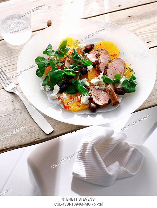 Plate of pork with pickled orange salad