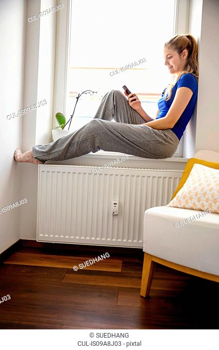 Young woman sitting on windowsill using cell phone