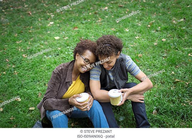 Two mature female friends drinking takeaway coffee in park