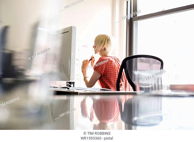 Office life. A young woman working at an office desk