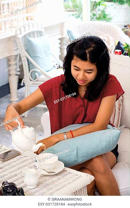 Asian woman pouring tea from the teapot into a white ceramic cup